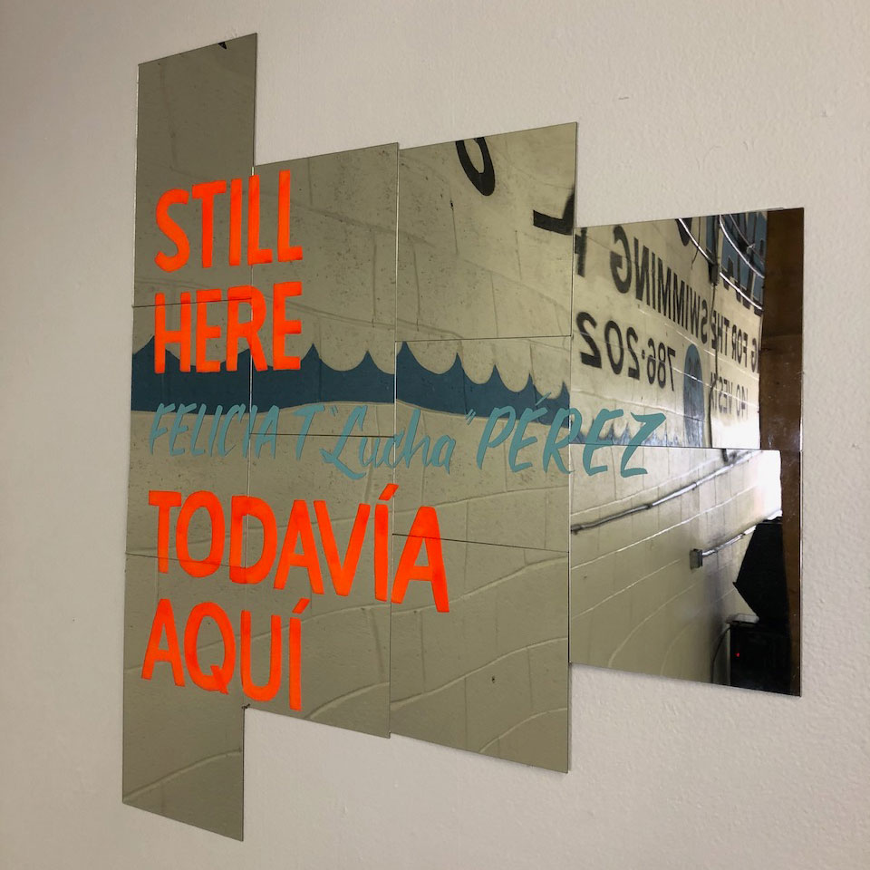 Picture of Lucha's art exhibit title on a mirror: Still Here Todavía Aquí